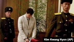 瓦姆比爾(中)星期一在北韓首都與一些北韓和外國記者見面,北韓警衛人員一直在他身旁。