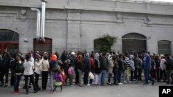 Des migrants attendent en file d'entrer dans le réfectoire dans un centre de réfugiés à Milan, Italie, 21 octobre 2016.