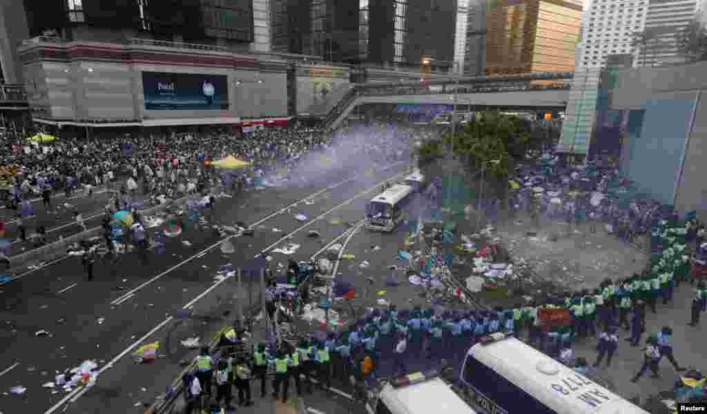 Protesters disperse as riot police fire teargas after thousands of protesters blocked the main street to the financial Central district outside the government headquarters in Hong Kong.