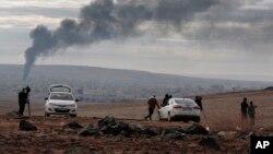 媒体在叙吕奇郊区山顶上观察叙利亚科巴尼战火