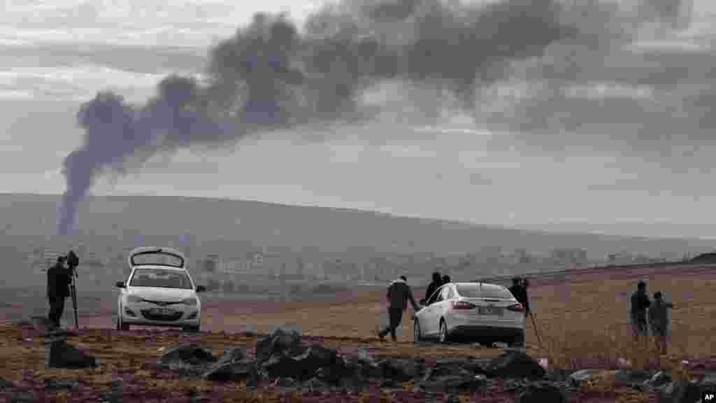 Truyền thông theo dõi trận chiến ở Kobani trên một ngọn đồi ở ngoại ô Suruc, biên giới Thổ Nhĩ Kỳ-Syria, ngày 19/10/2014.