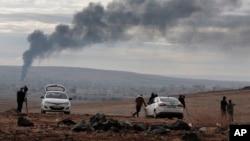 10月19日,新聞媒體在位於敘利亞和土耳其邊境的一個山頭拍攝被聯軍轟炸的地區冒起的濃煙。