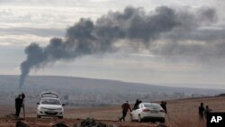 Asap membumbung setelah serangan udara di Kobani, Suriah, dalam pertempuran antara Kurdi dan militan Negara Islam atau ISIS, 19 Oktober 2014.