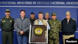 Colombia's President Juan Manuel Santos, center, speaks during a news conference in Bogota, Nov. 16, 2014.