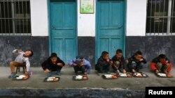 Học sinh ăn trưa ngoài trời tại trường tiểu học ở làng Đồng Quan, tỉnh Quý Châu ở Trung Quốc.