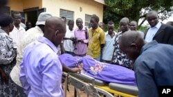 FILE - Relatives and other mourners watch as the body of South Sudanese journalist Peter Julius Moi is taken into the mortuary in Juba, South Sudan, Aug. 20, 2015.