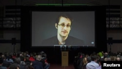FILE - Former U.S. National Security Agency contractor Edward Snowden appears live via video during a student-organized world affairs conference at the Upper Canada College private high school in Toronto, Feb. 2, 2015.