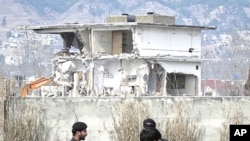Policemen and residents stand near while demolition work is carried out on the building where al Qaeda leader Osama bin Laden was killed by U.S. special forces last May, in Abbottabad, February 26, 2012.
