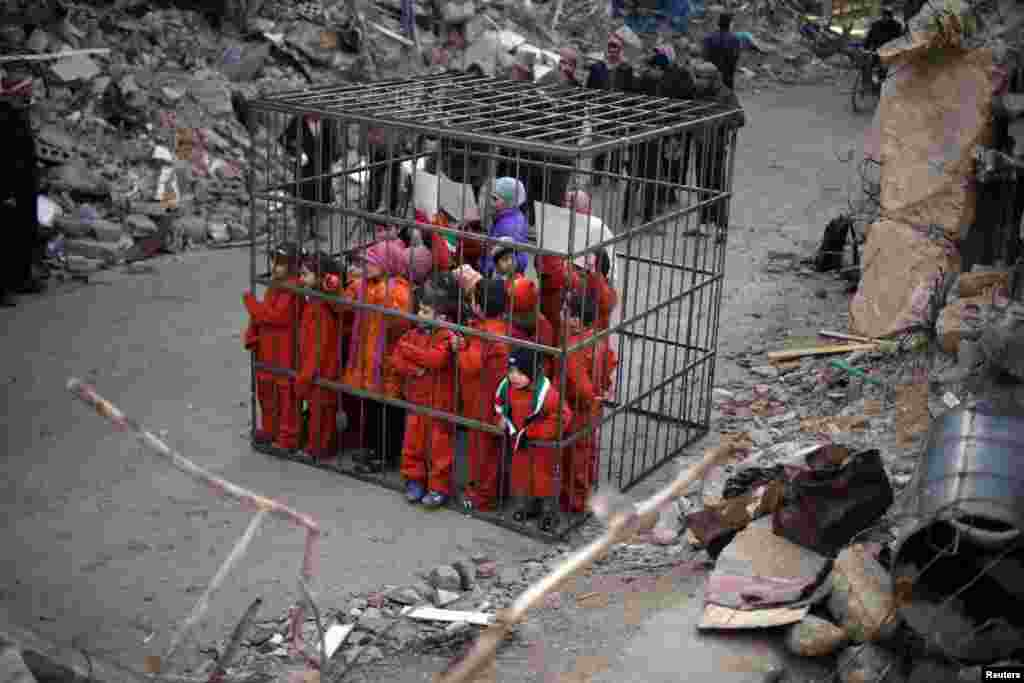 Children wearing orange suits depicting victims of the Islamic State carry banners inside a cage during a protest against forces loyal to Syria's President Bashar al-Assad, in Douma Eastern Al-Ghouta, near Damascus.