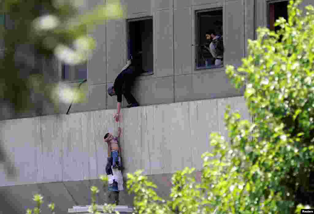 A boy is evacuated during an attack on the Iranian parliament in central Tehran.