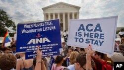 Supporters of the Affordable Care Act hold up signs as the opinion for health care is reported outside of the Supreme Court in Washington, June 25, 2015. (AP Photo/Jacquelyn Martin)