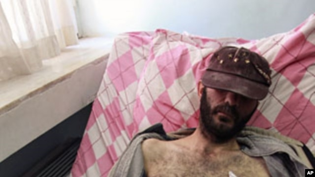 A fighter from the Free Syrian Army lies on a hospital bed in the southern town of Reyhanli in Hatay province on the Turkish-Syrian border, March 20, 2012.