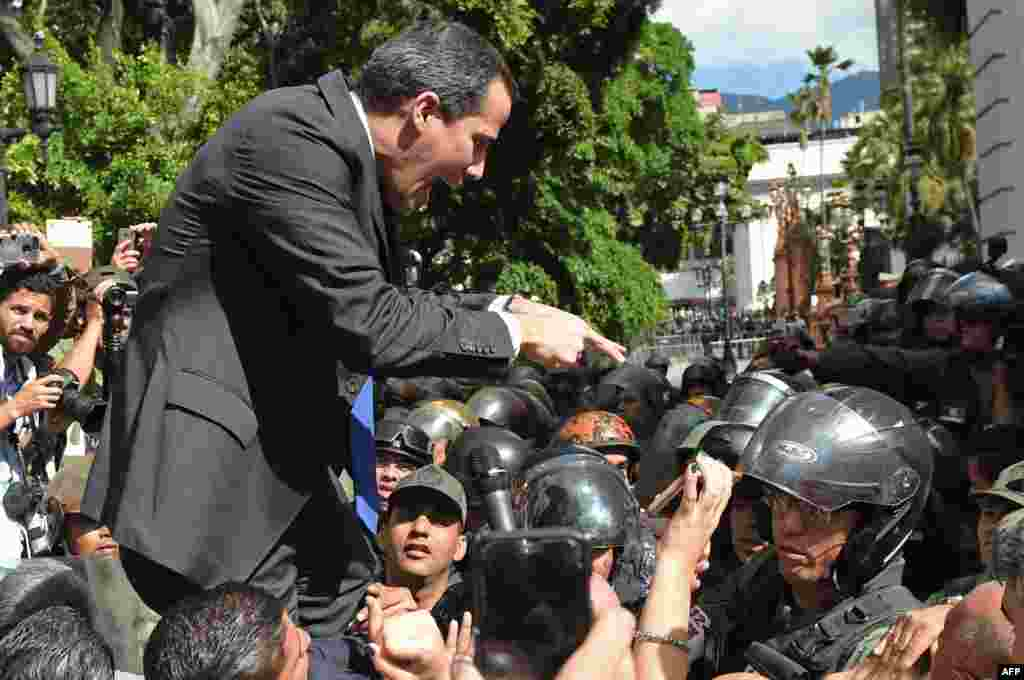 Venezuelan opposition leader and self-proclaimed acting president Juan Guaido confronts Bolivarian National Guard members upon arrival at the National Assembly, in Caracas.