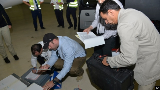 Samples brought back by the U.N. chemical weapons inspection team are checked in upon their arrival at The Hague, Netherlands, August 31, 2013.
