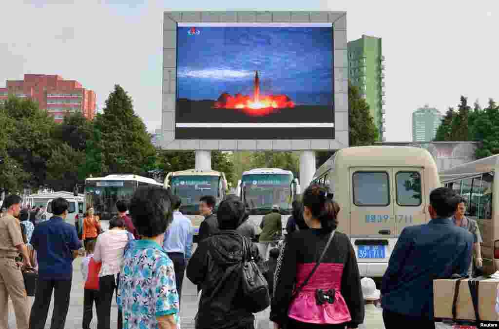 평양 시민들이 거리에 설치된 대형 스크린을 통해 화성-12 발사 성공 소식을 시청하고 있다.