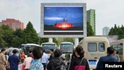 """朝鲜人在平壤车站观看关于朝鲜发射""""火星12""""导弹的电视新闻(2017年8月30日)"""