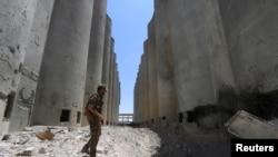 ARSIP – Pejuang Syrian Democratic Forces (SDF) berjalan di antara silo dan pabrik di Manbij setelah SDF mengambil alih fasilitas tersebut (1/7). Kegubernuran Aleppo, Suriah. (foto: REUTERS/Rodi Said)