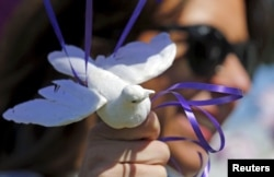 Jennifer Gordon holds a fabric dove at the base of balloons as she pays tribute to musician Prince at a makeshift memorial outside the fence of Paisley Park, his home and recording studio, in suburban Minneapolis, Minnesota, April 22, 2016.