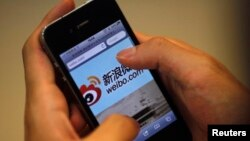FILE - A man holds an iPhone as he visits China's Weibo microblogging site in Shanghai, May 29, 2012. Weibo has partnered with U.S.-based rating agency Nielson's to gauge marketing possibilities on the platform.