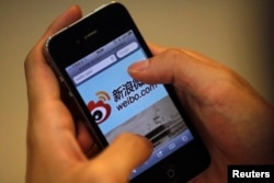 FILE - A man holds an iPhone as he visits Sina's Weibo microblogging site in Shanghai, May 29, 2012.