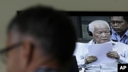 A journalist listens to Khieu Samphan, center, former Khmer Rouge head of state, as he appears on TV screen at the court press center of the U.N.-backed war crimes tribunal in Phnom Penh, file photo.