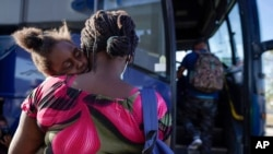 FILE - A woman and child prepare to board a bus to San Antonio moments after a group of migrants, many from Haiti, were released from custody upon crossing the Texas-Mexico border in search of asylum in Del Rio, Texas, Sept. 22, 2021.