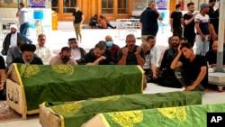 Des personnes en deuil prient près des cercueils des patients atteints de coronavirus qui ont été tués dans l'incendie d'un hôpital, à Najaf, en Irak, dimanche 25 avril 2021.