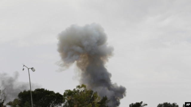 Smoke rises after an explosion, the cause of which was unclear, on Misrata's western front line, June 11, 2011