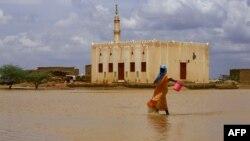 Une soudanaise traverse une zone inondée, à la suite d'inondations et de pluies torrentielles, dans la ville d'Osaylat, à 50 km au sud-est de la capitale Khartoum, le 6 août 2020.