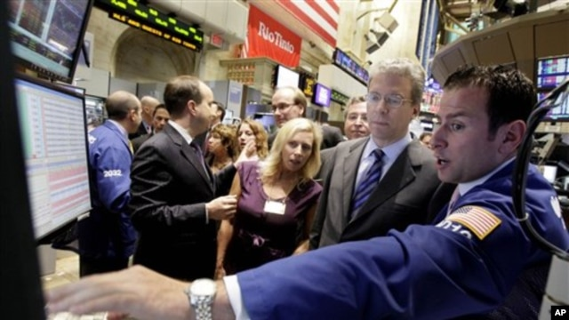Rio Tinto CEO Tom Albanese, second from right, talks with specialist Michael Pistillo, right, as he visits the post that trades his company's stock on the floor of the New York Stock Exchange, 6 Oct 2010