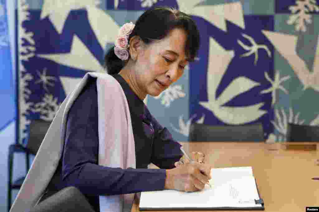 Aung San Suu Kyi signs the guest book of UN Secretary-General Ban Ki-Moon at the United Nations in New York, September 21, 2012.