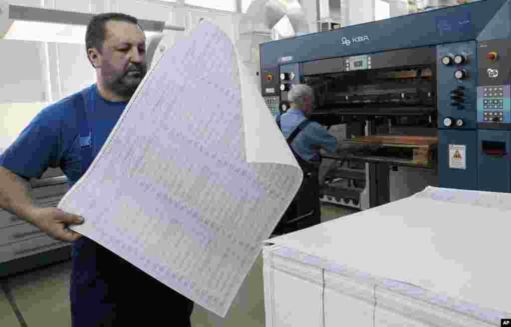 A worker at the state-owned printing house inspects a ballot for the May 25 snap presidential elections with 21 candidates taking part, in Kyiv, May 14, 2014.
