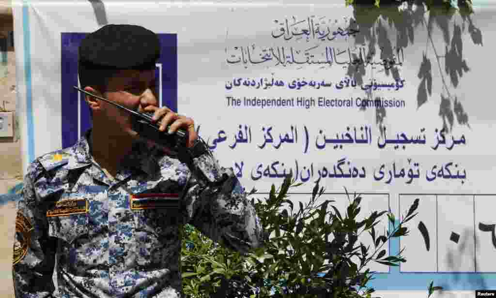 A policeman speaks on his walkie talkie at a polling centre in Baghdad April 19, 2013. The Iraqi government has tightened its security measures as the country prepares to provincial elections.