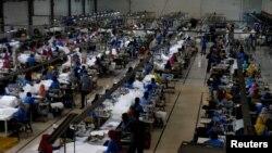Buruh pabrik tekstil yang biasanya memproduksi celana jeans, dikayrakan untuk membuat pakaian pelindung di tengah pandemi COVID-19 di Malang, 6 April 2020. (Foto: Antara via REUTERS)