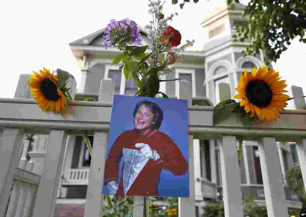 "A photo of the late actor Robin Williams as Mork from Ork hangs with flowers left by people paying their respects, in Boulder, Colorado, Aug. 11, 2014, at the home where his hit 1980s TV series ""Mork & Mindy"", was set."