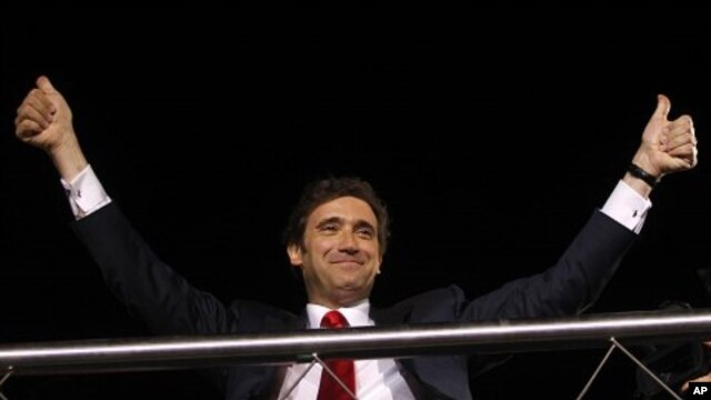Pedro Passos Coelho, leader of the center-right Social Democratic Party, PSD, gestures to supporters from the top of an open deck bus in Lisbon after his party won Portugal's general elections, June 5 2011