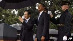 U.S. President Barack Obama and South Korean President Lee Myung-bak (L) are sheltered from the rain by U.S. military personnel (R) holding umbrellas on the South Lawn of the White House in Washington, October 13, 2011.