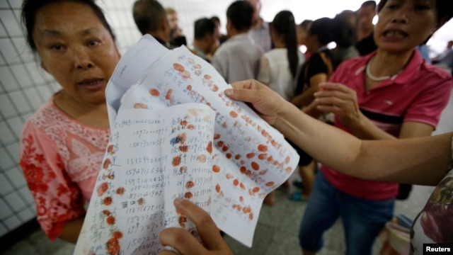FILE - A woman shows petitioning papers bearing petitioners' thumbprints to Reuters journalists near the State Bureau For Petitions and Visits, which handles applications from petitioners from all over China.