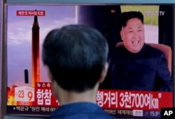 "FILE - A man watches a TV screen showing file footage of North Korea's missile launch and North Korean leader Kim Jong Un, at the Seoul Railway Station in Seoul, South Korea, Sept. 15, 2017. Former U.S. top diplomat Henry Kissinger has called North Korea's nuclear program the ""most immediate challenge to international security."""