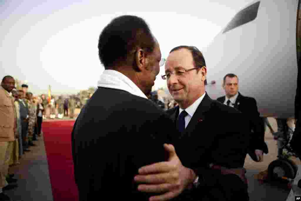 French President Francois Hollande, center right, is greeted by Mali's President Dioncounda Traore, as he arrives at the airport in Sevare, Mali, en route to Timbuktu, February 2, 2013.