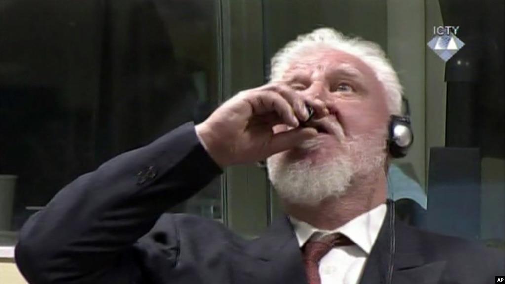 """Trong bức ảnh của Tòa án Hình sự Quốc tế hôm 29/11/2017, ông Praljak đưa một chai nhỏ lên miệng, trước phiên tòa xét tội ác chiến tranh ở La Haye, Hà Lan. Ông hét: """"Tôi không phải là tội phạm chiến tranh"""" (ICTY via AP)"""