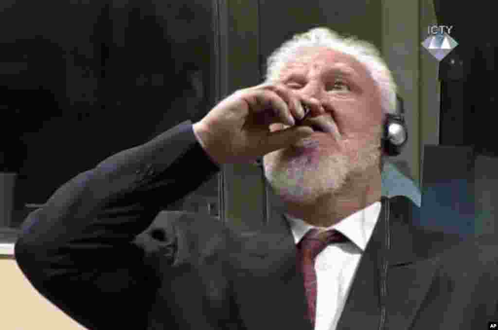 In this photo provided by the ICTY, former Bosnian Croat military commander Slobodan Praljak (C) appeared to dring poison seconds during a Yugoslav War Crimes Tribunal in The Hague, Netherlands, after judges upheld his 20-year prison sentence for involvement in a campaign to drive Muslims out of a would-be Bosnian Croat ministate in Bosnia in the early 1990s.