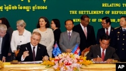 FILE - Australian Immigration Minister Scott Morrison, front left, signs a document together with Cambodian Interior Minister Sar Kheng, front right, during a ceremony for a controversial deal to resettle refugees in Phnom Penh, Cambodia, Sept. 26, 2014