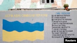 FILE - A Russian serviceman stands guard behind a wall featuring Ukraine's national flag and words of its national anthem at the Belbek Sevastopol International Airport in Crimea, March 4, 2014.
