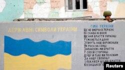 俄罗斯军人在克里米亚国际机场的一堵墙后面站岗,墙上画着乌克兰国旗,写着乌克兰国歌歌词