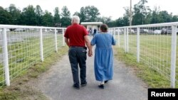 FILE - A couple leaves a free clinic that provides vision, dental and other health services in Wise, Virginia.