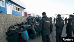 Russian police detain migrant workers during a raid on October 14, 2013.