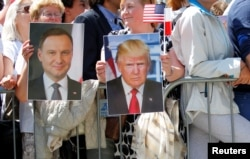FILE - People hold images of Polish President Andrzej Duda and U.S. President Donald Trump during Trump's public speech at Krasinski Square, in Warsaw, Poland, July 6, 2017.