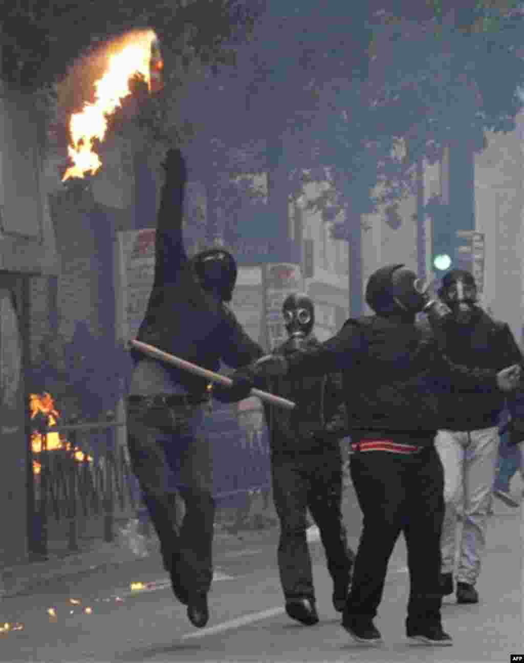 A protester throws a petrol bomb at riot police during clashes in Athens, Wednesday, Dec. 15, 2010. Hundreds of protesters clashed with riot police across central Athens Wednesday, smashing cars and hurling gasoline bombs during a massive labor protest ag