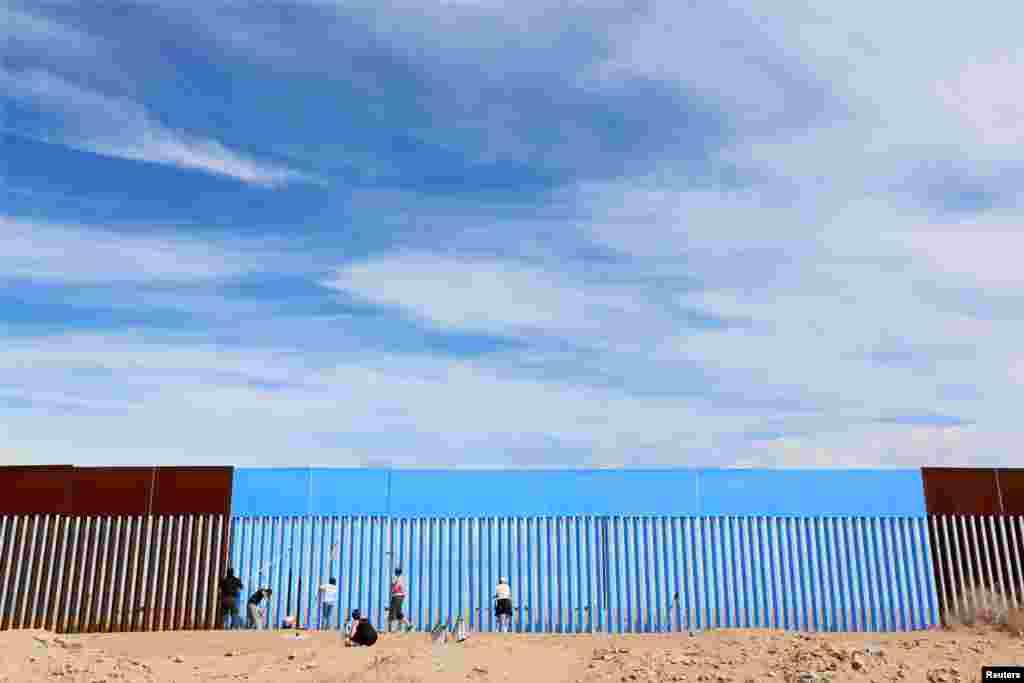 អ្នកស្ម័គ្រចិត្តផាត់ពណ៌ជញ្ជាំងព្រំដែនរវាងសហរដ្ឋអាមេរិក និងប្រទេសម៉ិកស៊ិក ដើម្បីបង្ហាញពីតម្លាភាព ក្នុងពេលនៃគម្រោង Erasing the Border Art នៅក្នុងក្រុង Mexicali ប្រទេសម៉ិកស៊ិក កាលពីថ្ងៃទី៩ ខែមេសា ឆ្នាំ២០១៦។